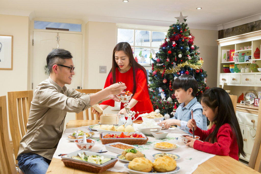 Image of a family of four sharing a meal in front of the Christmas tree